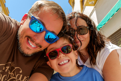 Family having fun wearing sunglasses & waving to a camera taking selfie photograph on summer holiday